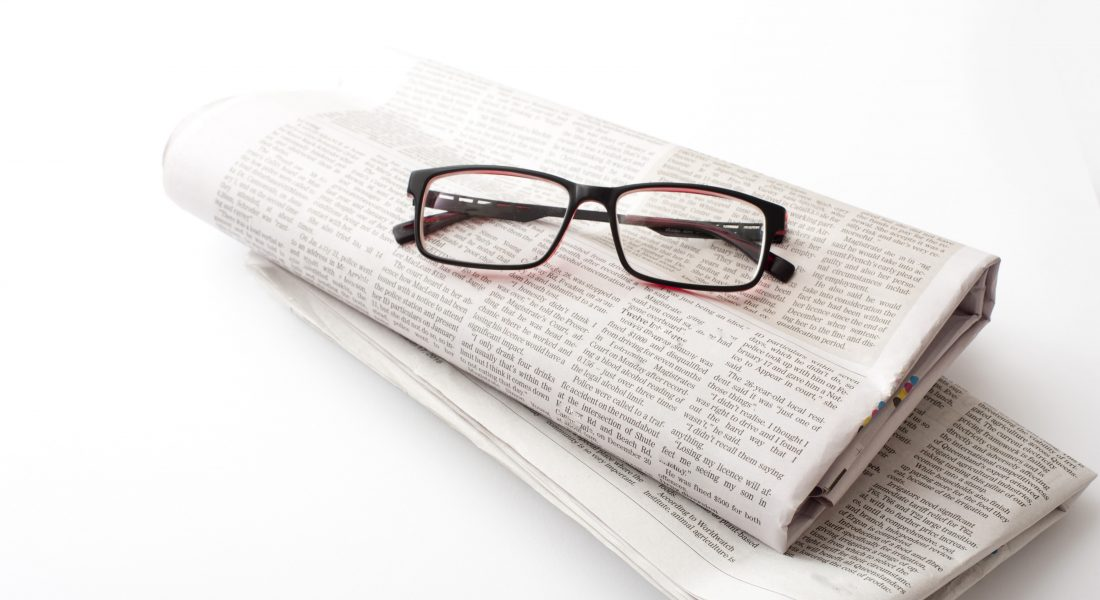 Reading glasses on a folded newspaper